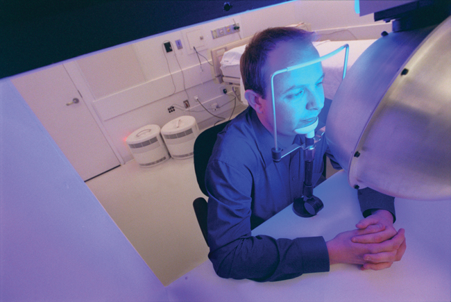 Steven Lockley seated in front of apparatus that is bathing his face in blue light