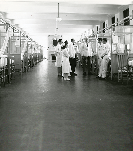 Image of mid-century photo, William Bosworth Castle, MD 1921 (center) talks with medical staff and faculty in a ward at Boston City Hospital