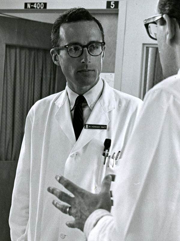 Howard Hiatt in white coat talking with colleague