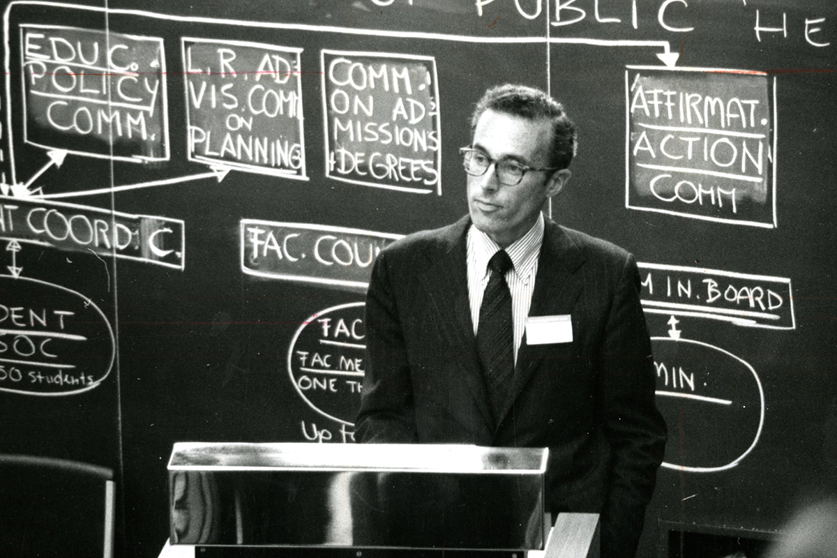 Howard Hiatt at lectern in front of a blackboard