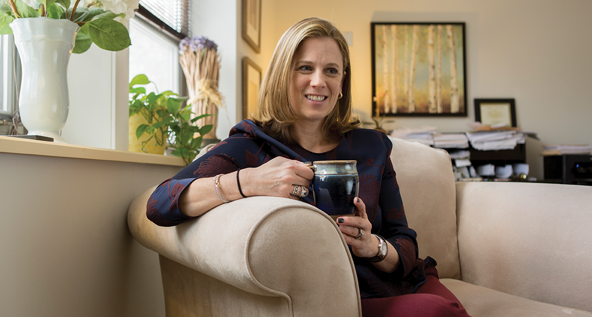 Kimberly Pearson seated on a couch holding a coffee mug