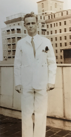 Perry Baird as a medical student, standing outdoors, wearing short white coat, pens in breast pocket