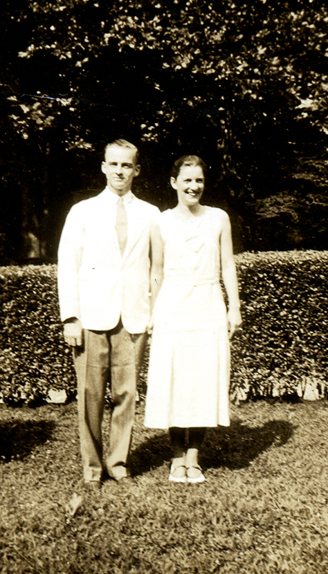 Perry and gretta Baird stand outdoors next to one another wearing summer whites, 1933