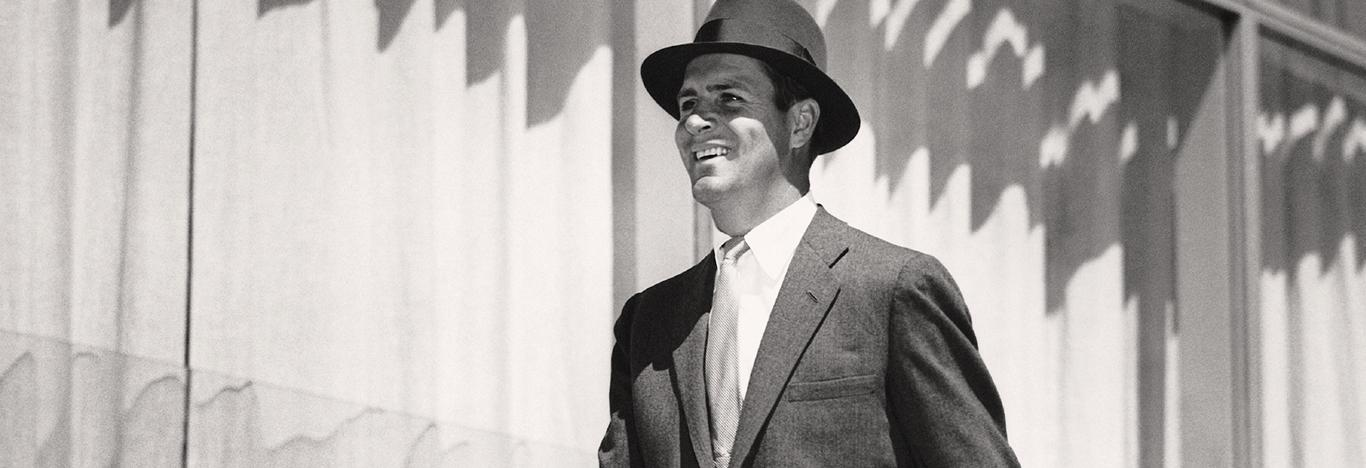 black and white photo of a smiling suited man wearing a fedora