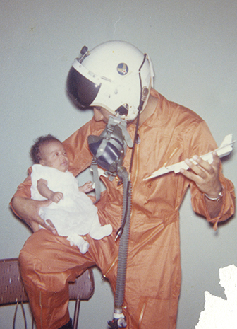 Pilot Fountain wiring flight suit and holding baby daughter, Tamara