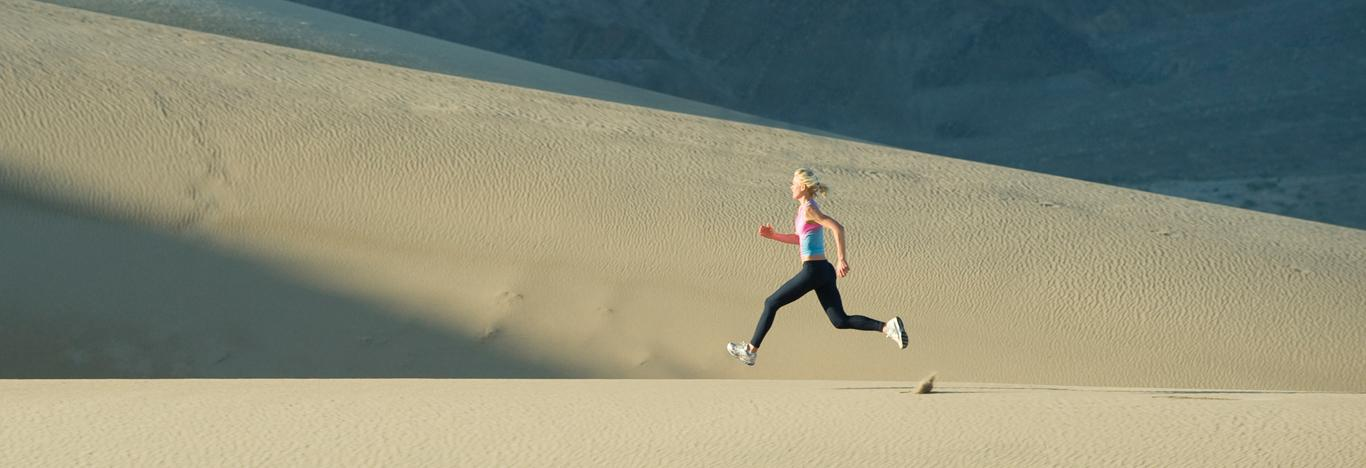 woman running along sand dunes