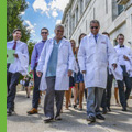 Students walking in white coats