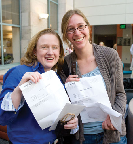Lauren Gilstrap (left) and Emily Whitesel show off their matches—Gilstrap will be staying local, with a match in internal medicine at Massachusetts General Hospital, while Whitesel will be headed to New York Presbyterian Hospital–Columbia University Medical Center to begin a residency in pediatrics. Photo by Suzanne Camarata.