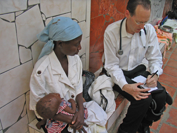 Paul Farmer with a young patient and mother in a clinic in rural Haiti. Photo courtesy Partners In Health.
