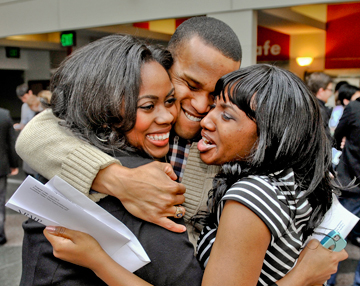 From left, Brittany Dixon, Cornell Cummings and Annika Barnett embrace after receiving their residency matches on March 15.  Photo by Steve Lipofsky