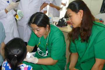 Tran, center, treating a patient at the clinic in Vietnam.  Image: Thanh-Nga Tran