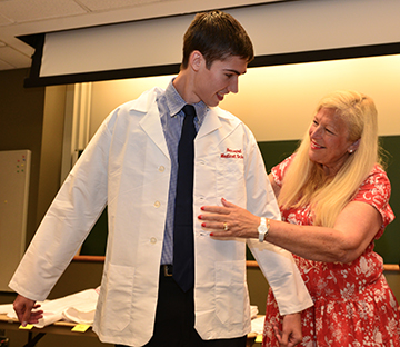 A student in the Francis Weld Peabody Society receives his new white coat. Image: Steve Lipofsky