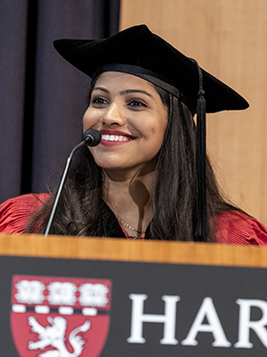 Young woman of South Asian descent smiling at podium