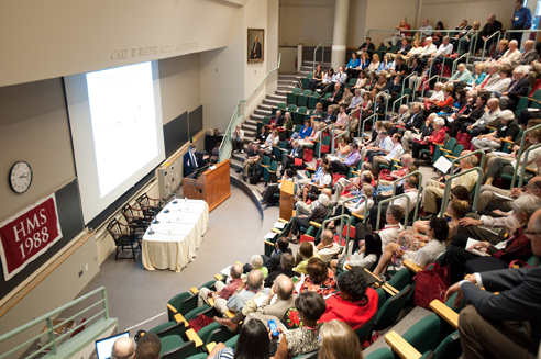 Lecture hall full of people listiening to a symposium