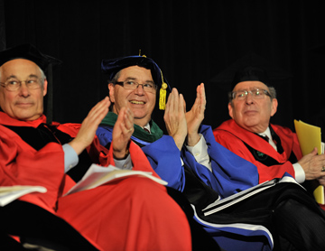 Donald Berwick (left), HMS Dean Jeffrey S. Flier (center) and HSDM Dean Bruce Donoff (right) applaud one of the student speakers.<br/>Photo by Steve Lipofsky.