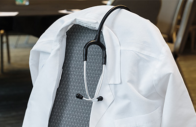 White coat and stethoscope hanging on a chair.