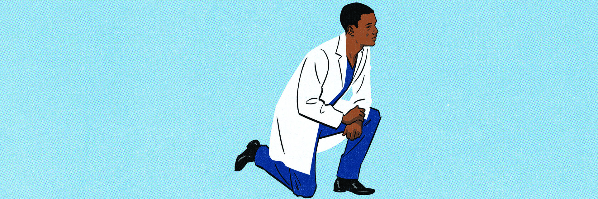 young man in a white coat taking a knee