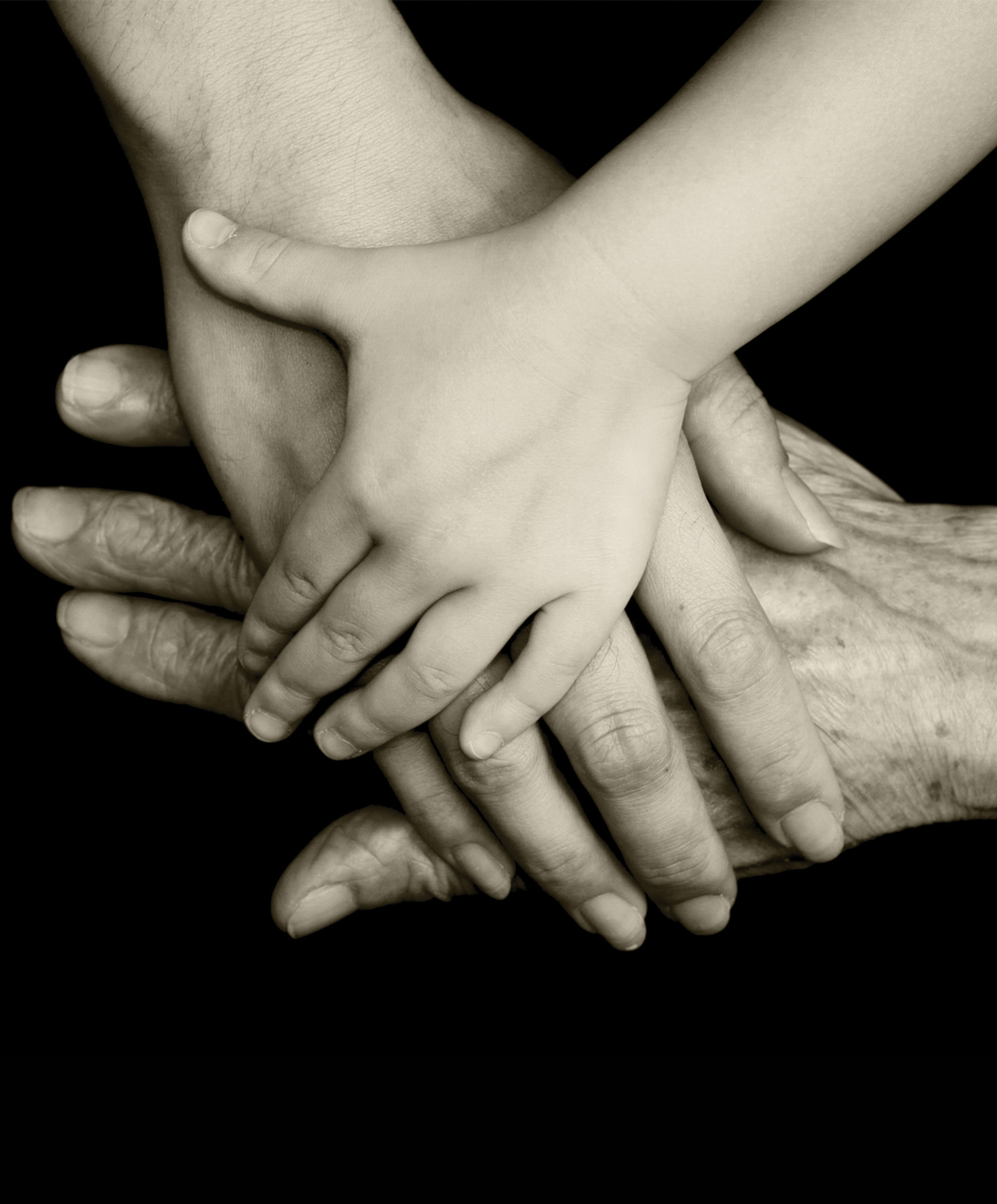 hands of three different people, three different ages, crossed