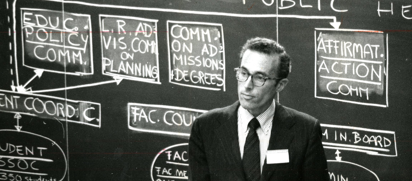 Howard Hiatt in front of a blackboard at the Harvard School of Public Health, circa 1970s