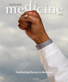 cover of winter issue showing raised fist of a Black man in white coat, fist slightly disrupting magazine logo