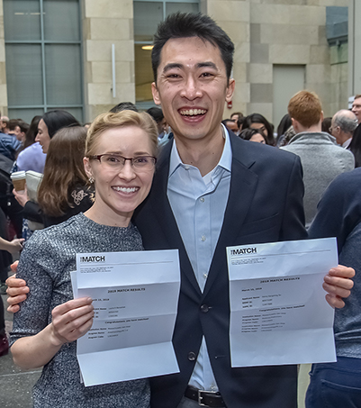 Laura Banashek (left) and Henry Su (right) holding up their Match Day letters, smiling
