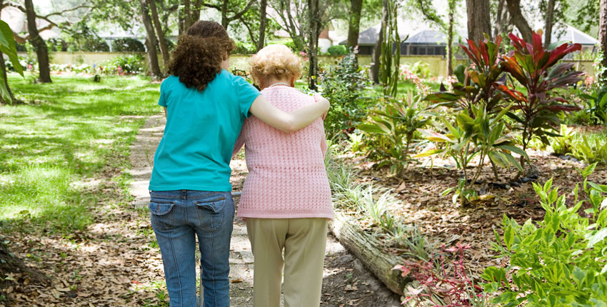 Caregiver walking with an elderly woman, photographed from behind