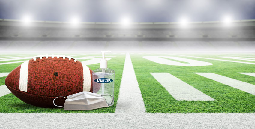 Photo of a football field with a ball, mask, sanitizer