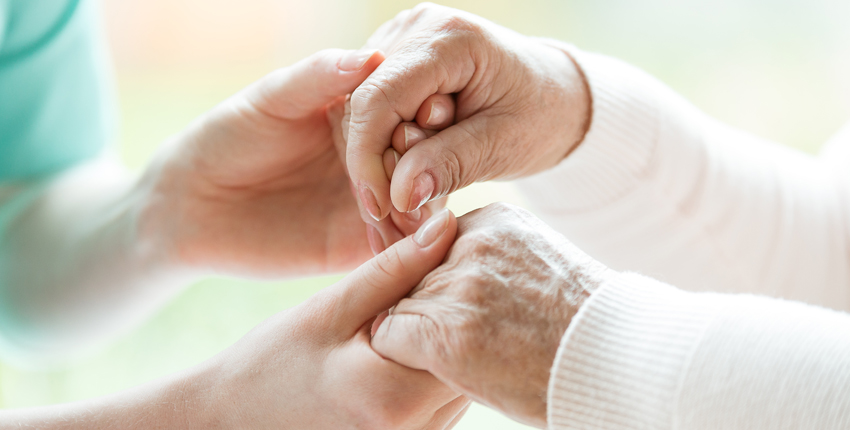 Image: a caregiver holding hands with a hospice patient