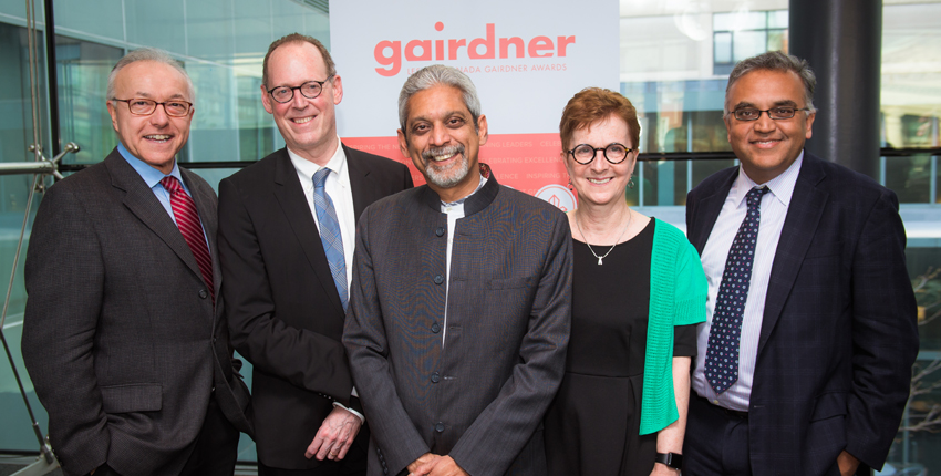 Four men and a woman smiling in front of a backdrop for the Gairdner Foundation.