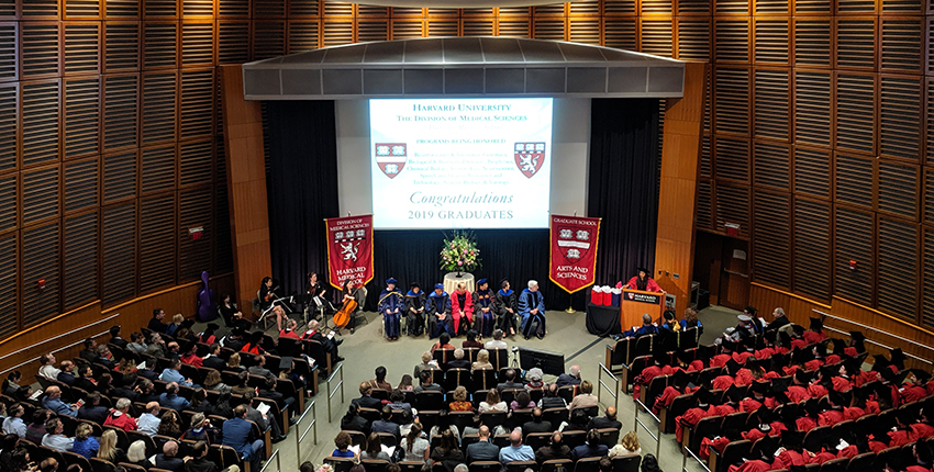 Auditorium with banners, program heads, graduates and guests