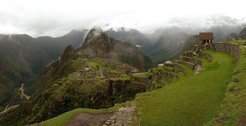 panorama of Machu Picchu site beneath cloudy sky