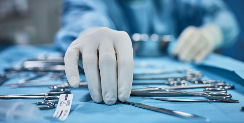 Hands reaching for surgical tools.