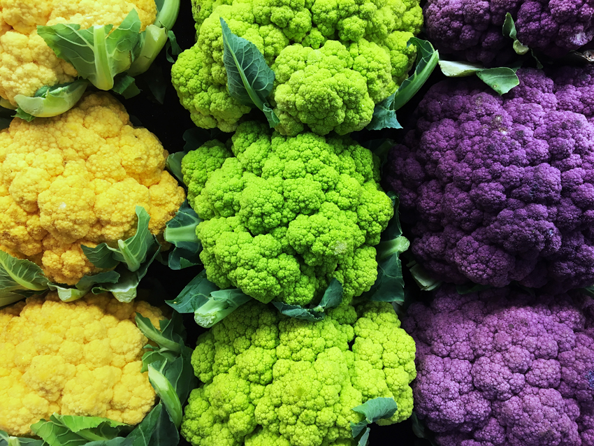 Brightly colored cauliflower crowns--yellow, green, purple
