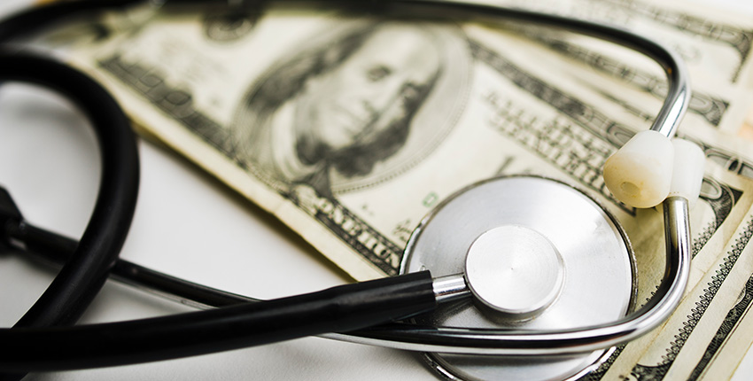 photo of stethoscope on top of money