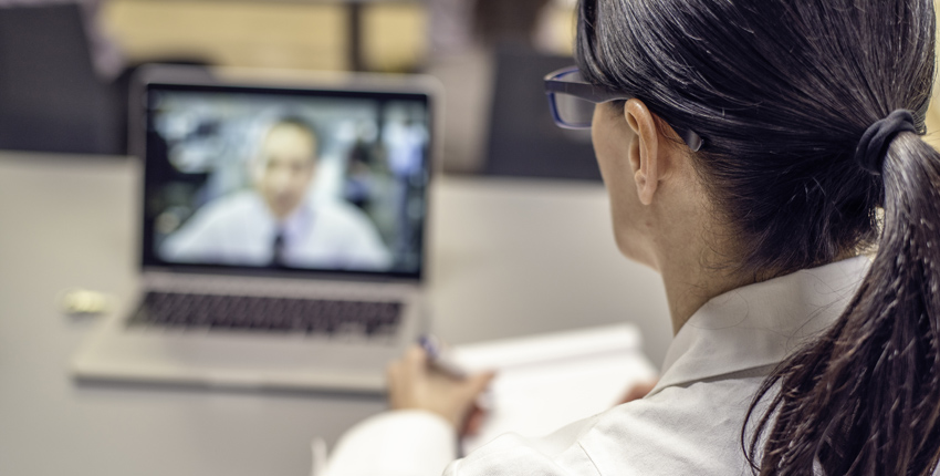 Looking over a doctor's shoulder, we see a patient video conferencing on the doctor's laptop.