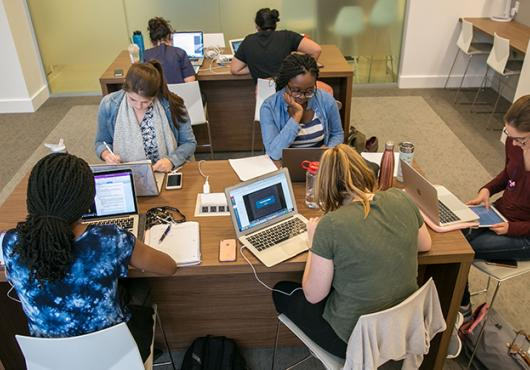 seven students studying at two desks in new student study center
