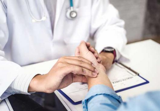 Stock image of a doctor's hands taking a patient's pulse