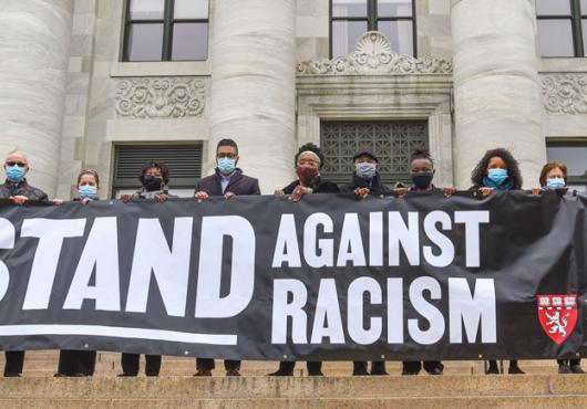 HMS community members holding a 'Stand Against RAcism' banner