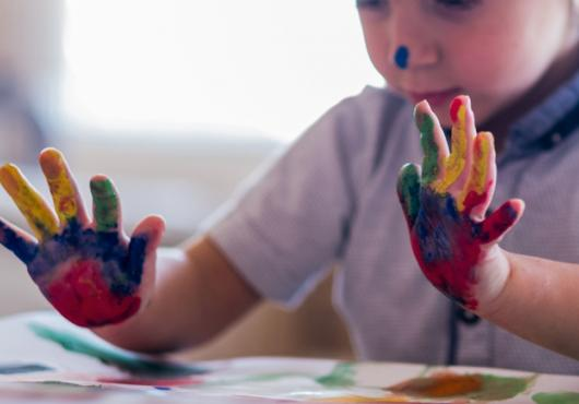 A young child's paint-covered hands.
