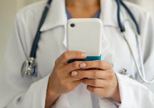 Female physician holding a mobile phone