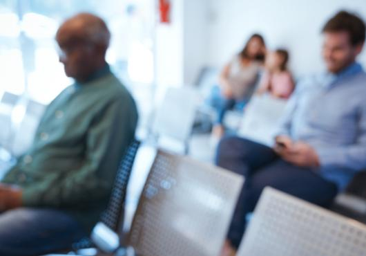 A blurry image of people in a waiting room.