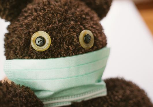 Photo of a teddy bear wearing a surgical mask