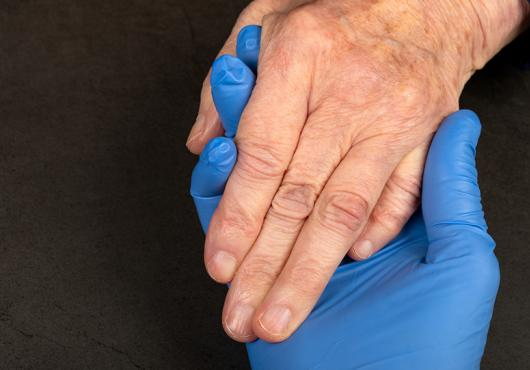 A hand in a blue latex glove holds the ungloved hand of an older white person