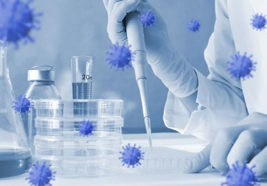 Photoillustration of coronavirus floating around lab equipment with person holding a pipette
