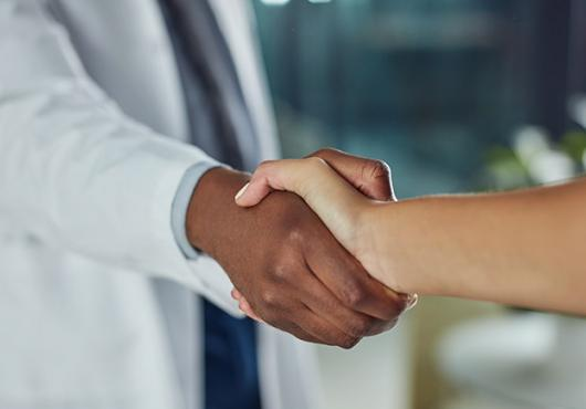 Doctor in a white coat shaking a patient's hand
