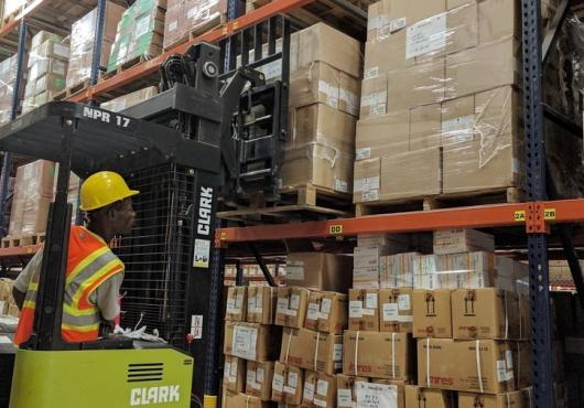 A man operates a forklift loaded with boxes in a warehouse.
