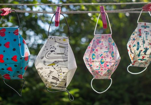 Diverse, colorful masks hang on a laundry line.