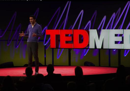 A man speaks on a stage, standing in front of a sign that says TEDMED.