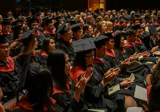 Audience shot of graduates in black and red regalia
