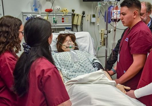 "Students care for a ""patient"" in a MEDscience simulation. Image by Steve Lipofsky"